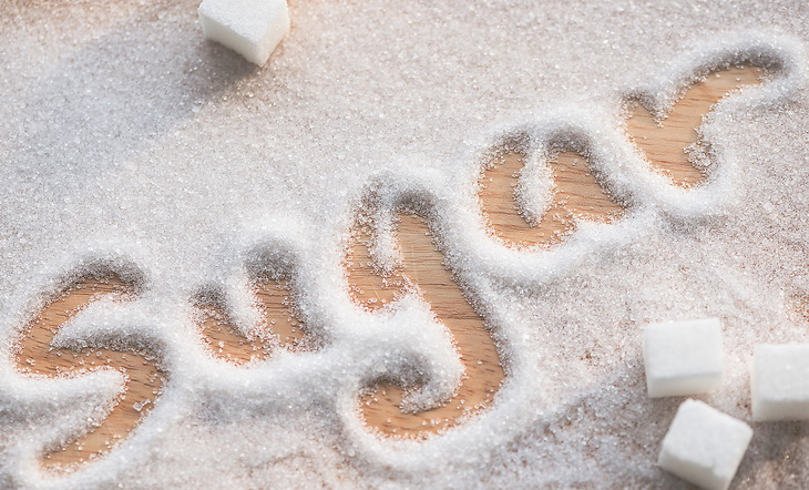 Inscription sugar made into pile of white granulated sugar