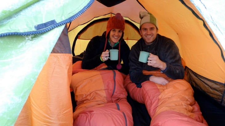 Young couple taking a picture in a tent