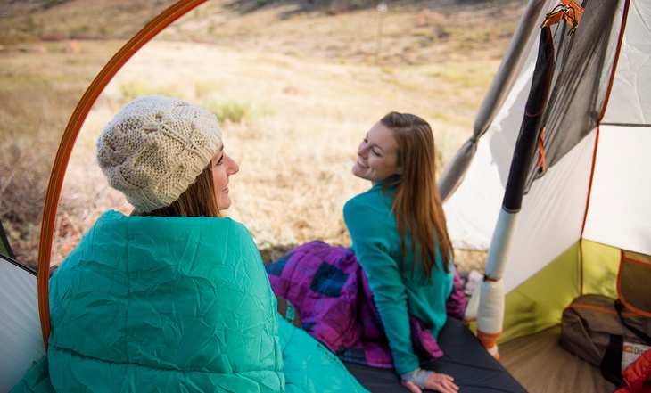 Two womens in sleeping bags laughing