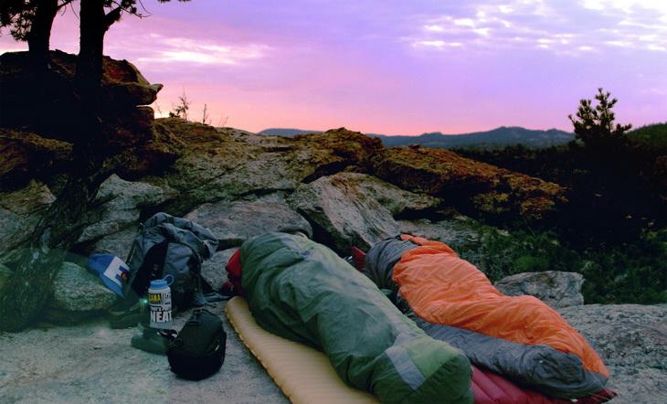 Two people in sleeping bags sleeping outside in the wild