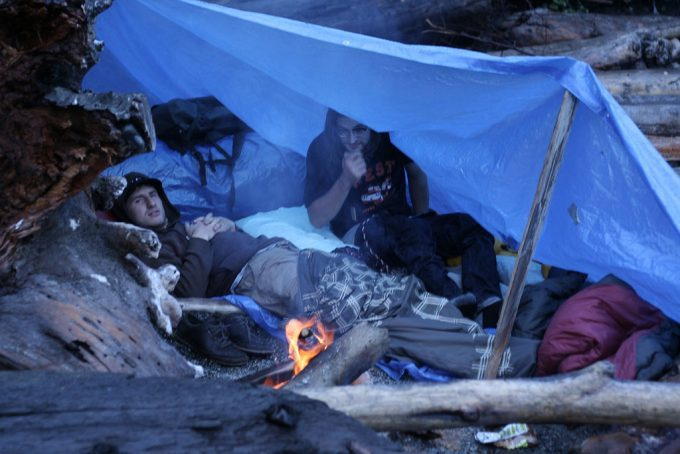 two-guys-under-tarp-tent-next-to-fire