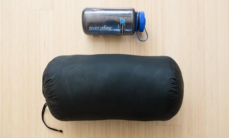 Western Mountaineering Kodiak sleeping bag ina storage sack and a bottle of water on the floor