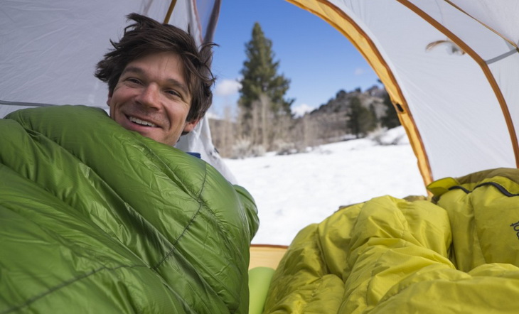 Man in a sleeping bag in tent smiling at the camera
