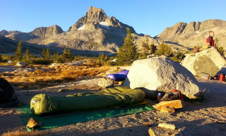 Western Mountaineering sleeping bag on the ground and mountains in the background