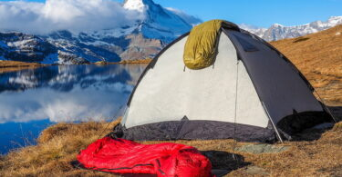 Two sleeping bags, a tent and the mountains in the background
