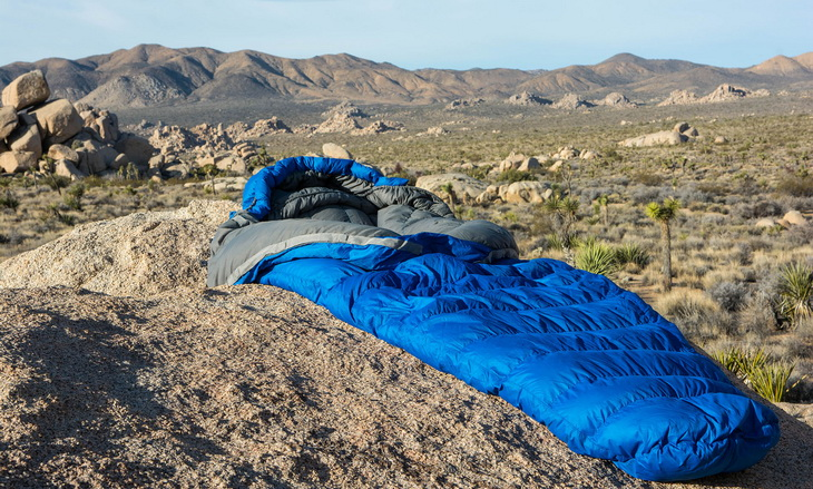 A sleeping bag on the ground and the mountains is the background