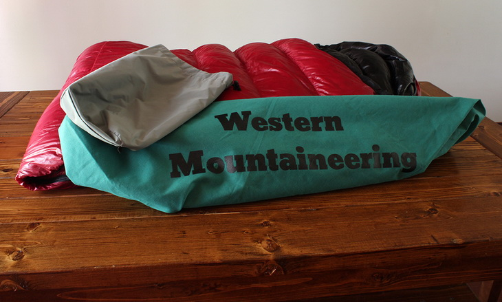 Western Mountaineering Sycamore sleeping bag on a brown wooden table