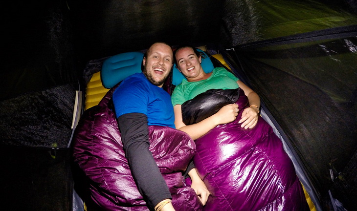 A couple in a tent sitting in Western Mountaineering Highlite Sleeping Bags