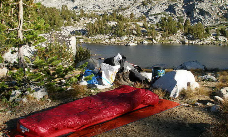 Western Mountaineering sleeping bag on the ground outside near a water and mountains