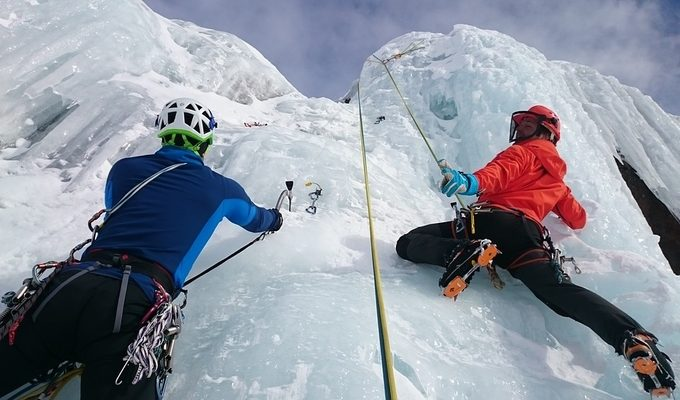Alpinists climbing an iced rock