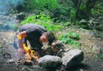 A man that has just started a fire outdoors