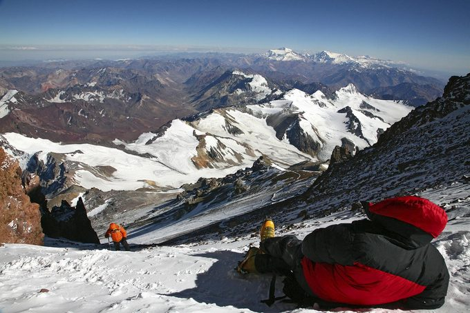 An exhausted climber rests and waits for a team member on summit