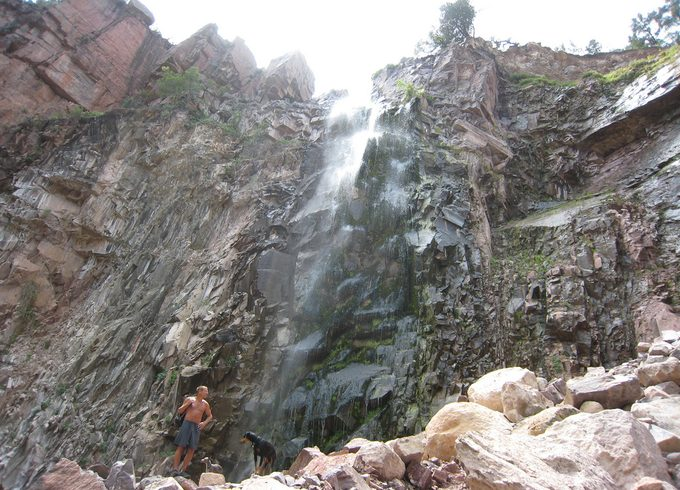 A man and a dog under the reavis falls in arizona