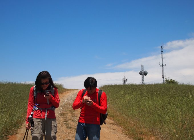Hikers being lost and watching their mobile devices