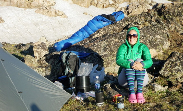 A woman looking at the camera and a sleeping bag at her back