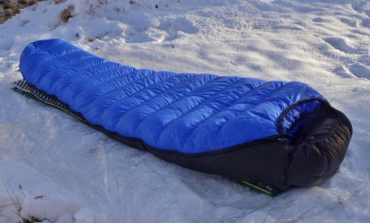 Western Mountaineering Ultralite Mummy Sleeping Bag laying on the snow