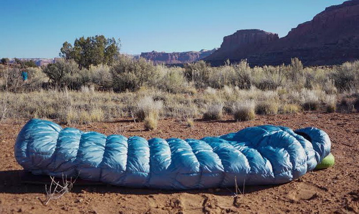sleeping bag on the ground and grand canyon in the background