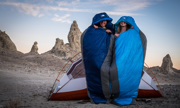 Two aduls in The North Face Cat's Meow Sleeping Bag near a tent outside