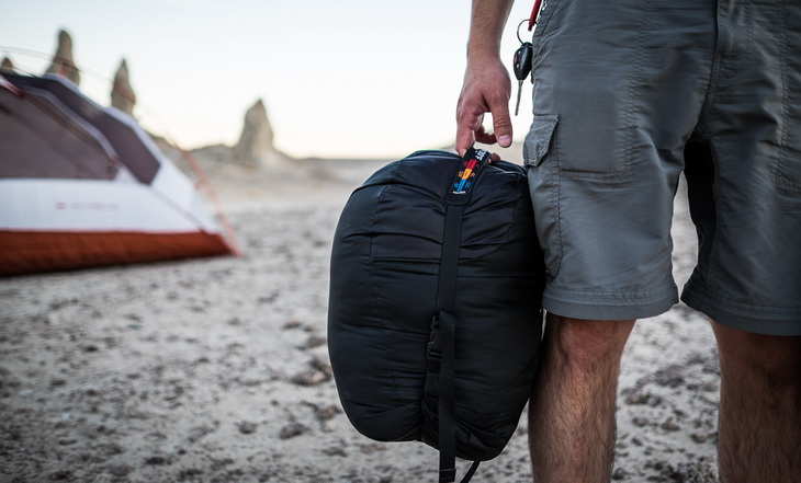 Man on a beach holding The North Face Cat's Meow Sleeping Bag