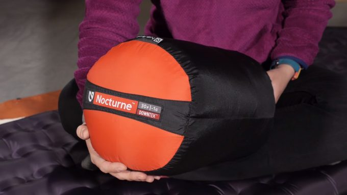 Image showing a woman holding the Nemo Nocturne Sleeping Bag packed