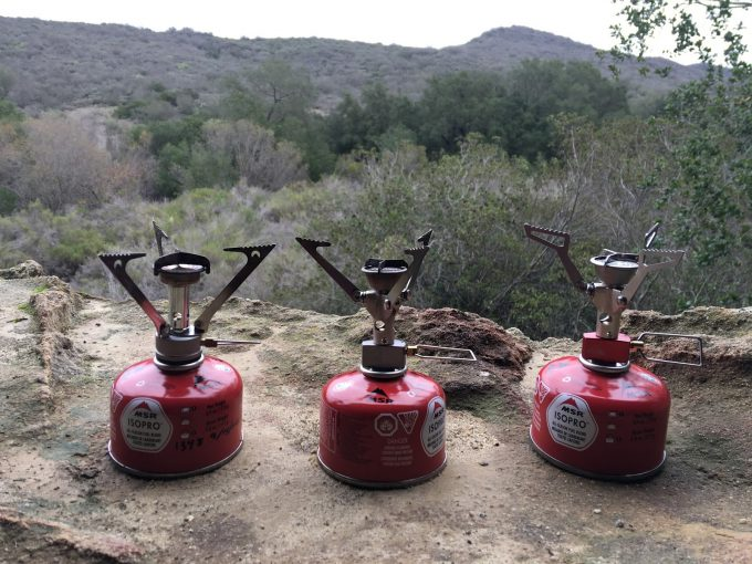 Image showing three A MSR PocketRocket Stove outside on the ground