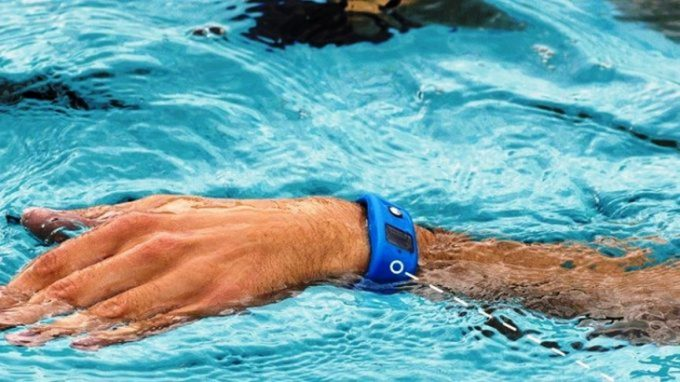 A man swimming in the pool while is wearing a waterproof-fitness-tracker