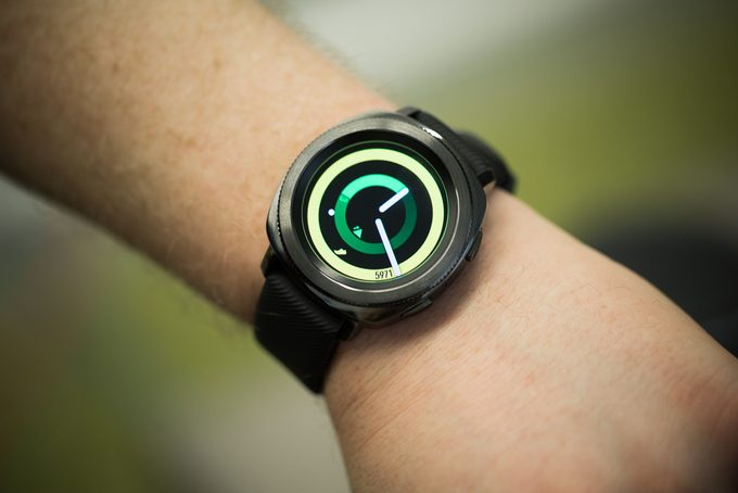 A black smartwatch worn on the left hand