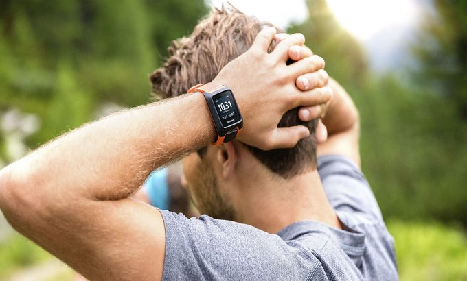 A runner with his hands on the head wearing a GPS fitness tracker