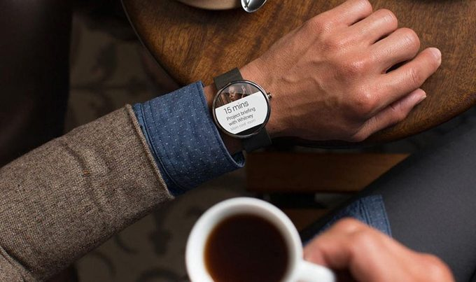 A man wearing his smartwatch while drinking coffee
