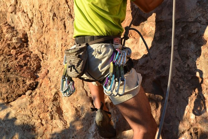 Man climbing rocks and wearing tactical belt and many accessories