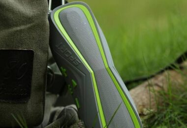 Sport silver-green wireless bluetooth speaker and a backpack on the grass