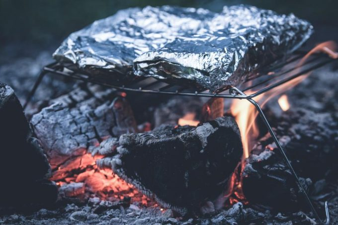 Food being cooked under aluminum foil