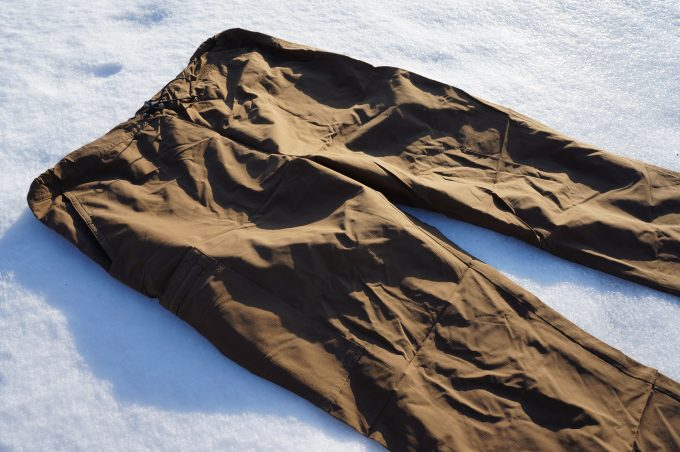 A pair of hiking pants lying on the snow