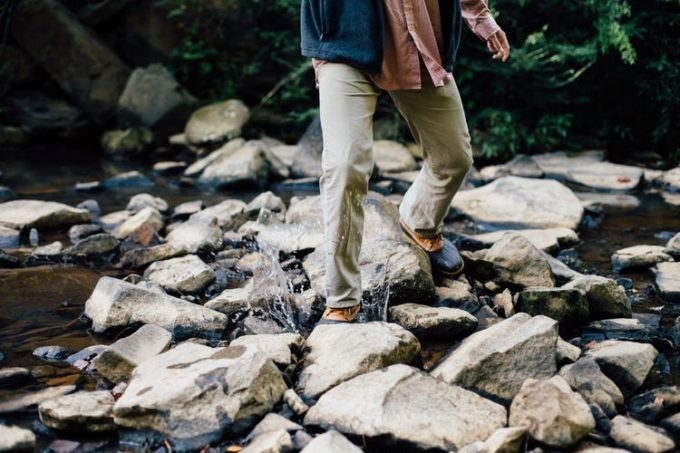 Man wearing hiking pants while crossing a river