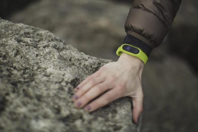 A person wearing a green tracker and holding on a rock