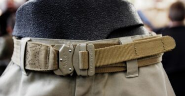 Brown tactical belt attached to a pair of pants in a store