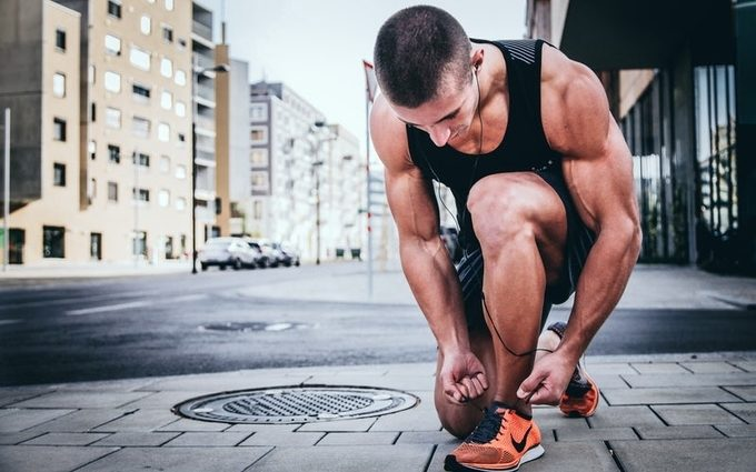 A man tying up his shoe lace and getting ready for a jog
