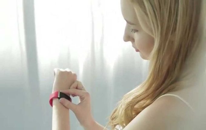 Girl wearing pink tracker on left hand