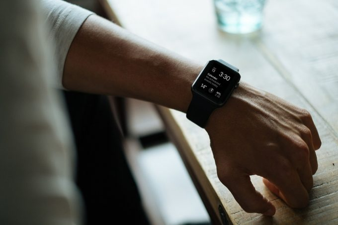 A black fitness tracker for iPhone worn on left hand