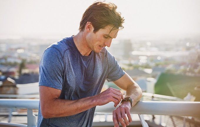Image of a man looking at his fitness watch track
