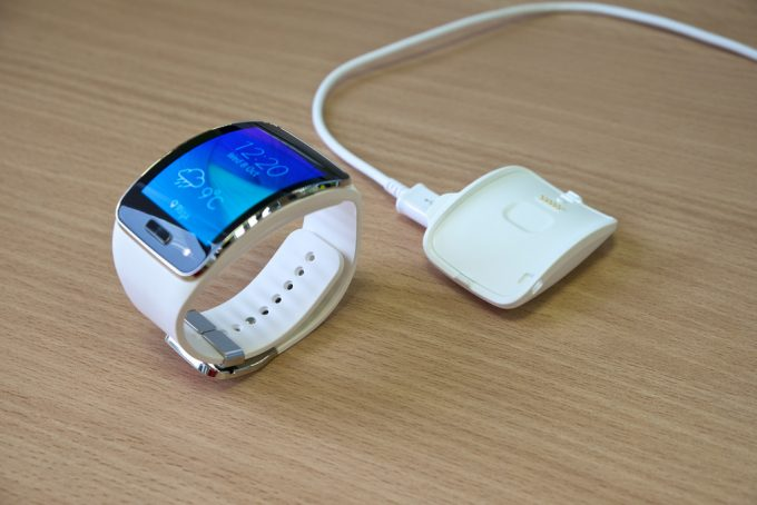 Image showing a white smartwatch and a charger on a table