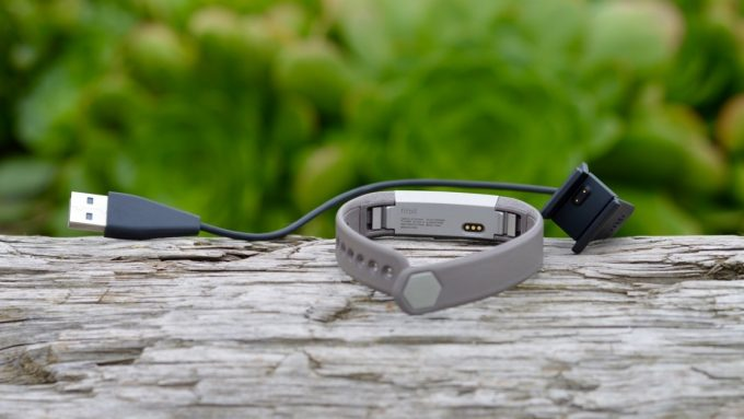 Image showing a fitbit-alta-charger and the watch on a wood