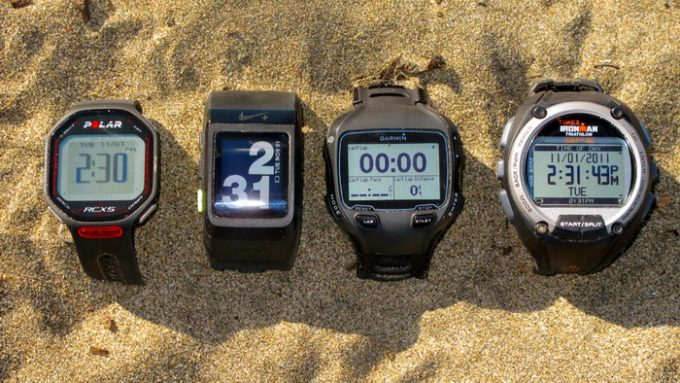 Image showing four different type of fitness watches in sands on a summer day