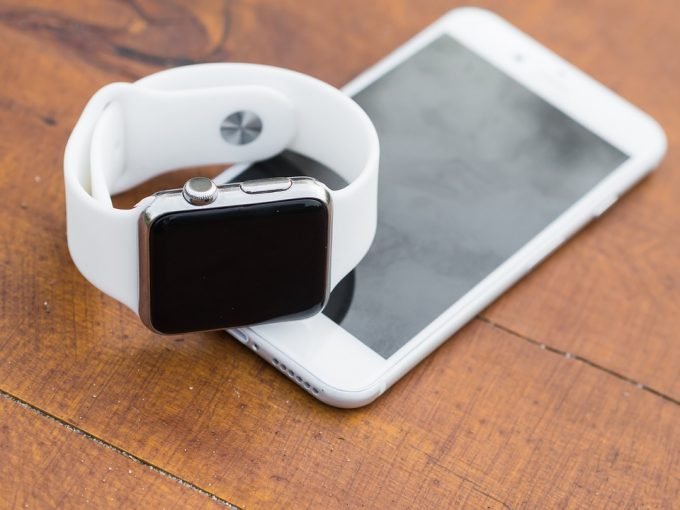 Image showing a white fitness watch and an iphone on the table