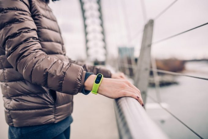 A person standing on a bridge and wearing a green smartwatch for iphone
