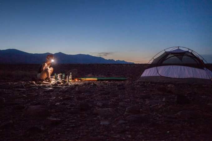 A camper outside their tent in the evening