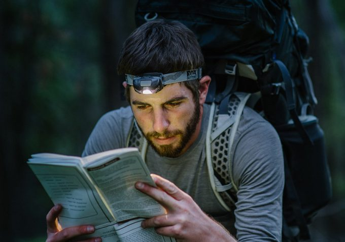 backpacker with headlamp reading a map