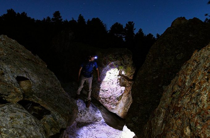 man between rocks wearing a headlamp