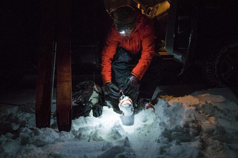 man in snow wearing headlamp