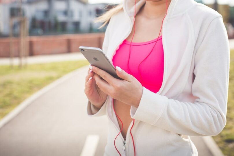 woman holding phone during workout